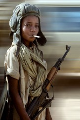 A child soldier poses with a libyan helm